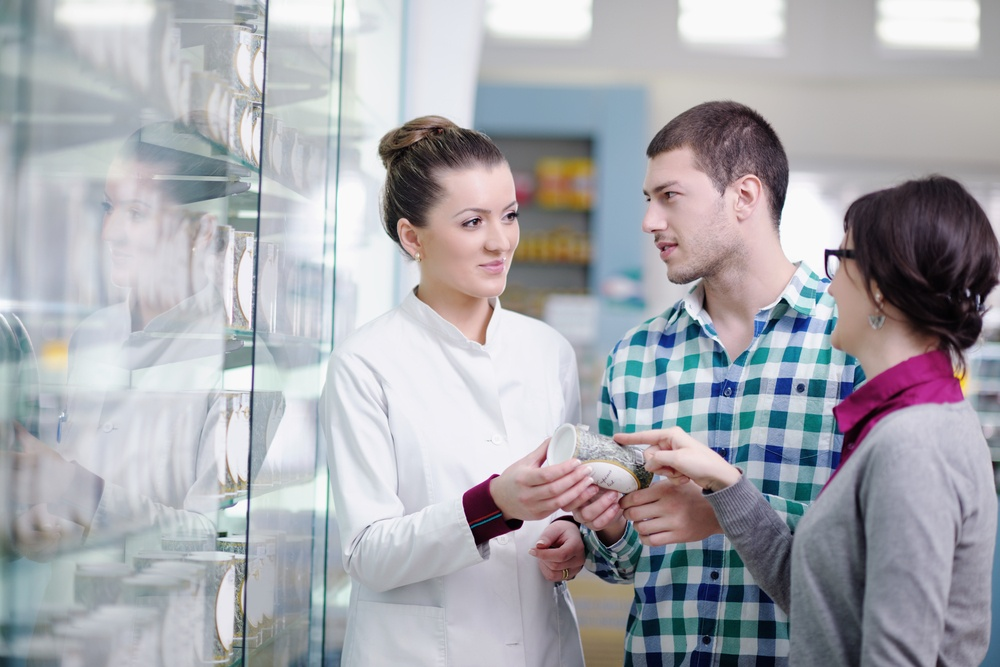young pharmacist suggesting medical drug to buyer in pharmacy drugstore.jpeg